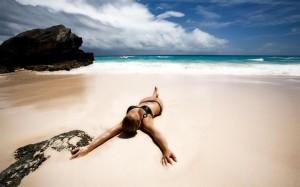 mujer tumbada en la playa relajacion
